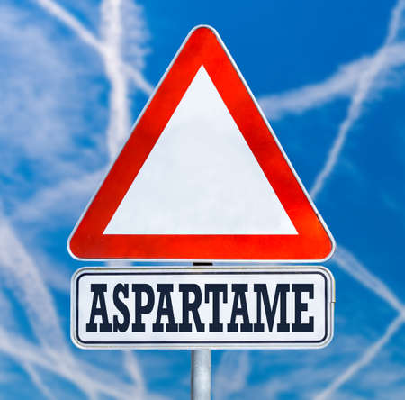 Conceptual image of a triangular white traffic warning sign with the word - Aspartame - a non-saccharide articifial sweetener which has long been debated over safety concerns, blue sky with contrails.