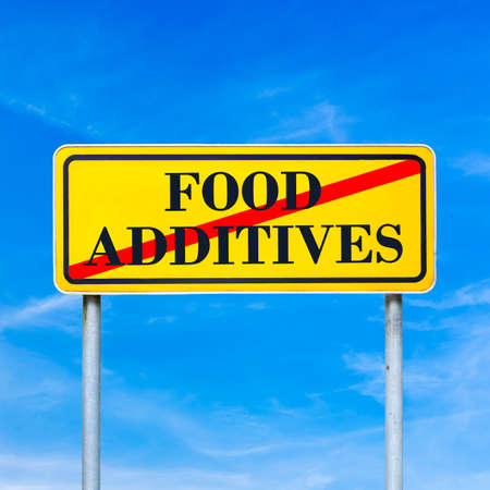 stabilizers: Food additives prohibited - conceptual image with the words Food additives crossed through in red on a yellow traffic sign against a sunny clear blue sky. Stock Photo