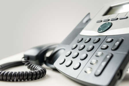 angled view: Close up angled view of a landline telephone instrument with a number pad and the handset or receiver off the hook in a communications concept.