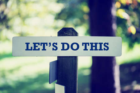 this: Old rustic signpost with the phrase Lets do this, outdoors in sunny woodland with a vintage instagram style filter effect. Stock Photo