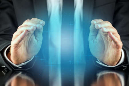 foretell: Magician with a crystal blue glow holding his hands protectively above it to feel the energy as he foretells or predicts the future conceptual of a fortune teller.  Stock Photo