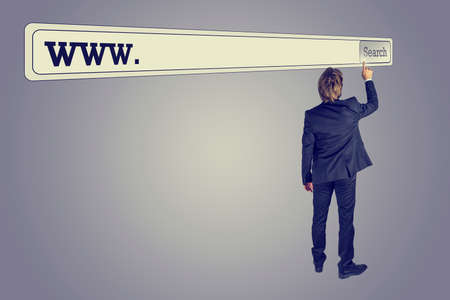 Rear view of a man wearing business suit searching for a web address touching the button of a huge virtual search bar placed above his head on retro grey background. photo