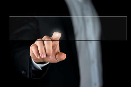 Close-up of the hand of a businessman wearing formal suit while touching a blank transparent virtual screen or a responsive futuristic interface. photo