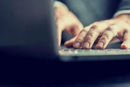 mecanograf�a: �ngulo de visi�n baja de la parte posterior de la computadora de un hombre de negocios a escribir en un teclado de la computadora port�til en una imagen de tonos de �poca retro. Foto de archivo