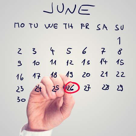 illicit: Mano maschile marcatura 26 giugno - Giornata internazionale contro l'abuso e il traffico illecito - sul calendario virtuale. Archivio Fotografico