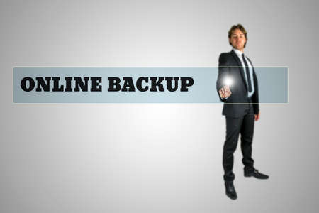 accessing: Stylish young businessman accessing Online Backup by touching a navigation bar on a virtual interface containing the words - Online Backup - over grey with copyspace below.