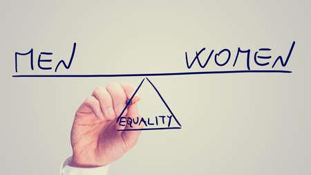 L'égalité entre les hommes et les femmes, une image conceptuelle de la situation des droits des femmes avec un homme tirant une bascule sur une interface virtuelle d'équilibrage de ces deux concepts sur les extrémités opposées en équilibre. Banque d'images