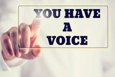 Phrase You have a voice on a virtual interface in a navigation bar with a businessman touching it with his finger from behind. Stock Photo