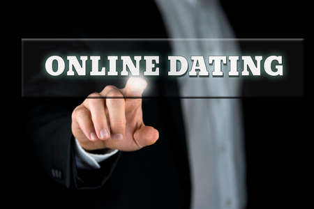matchmaker: Online dating button on virtual screen with male hand activating it from behind.