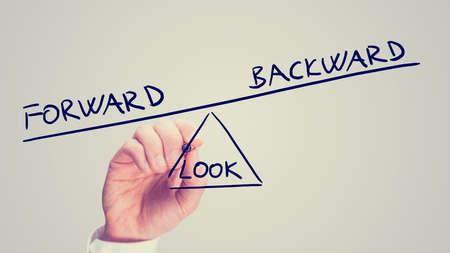 imbalance: Retro stijl vervaagde beeld van een man het tekenen van een wip met de woorden Look Forward - Backward in onbalans in het voordeel van het kijken vooruit in het leven. Stockfoto