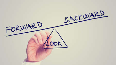 backward: Retro style faded image of a man drawing a seesaw with the words Look Forward - Backward in imbalance weighted in favor of looking forwards in life.