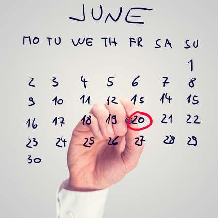 标志6月20日的男性手 - 世界难民日 - 在虚屏上。