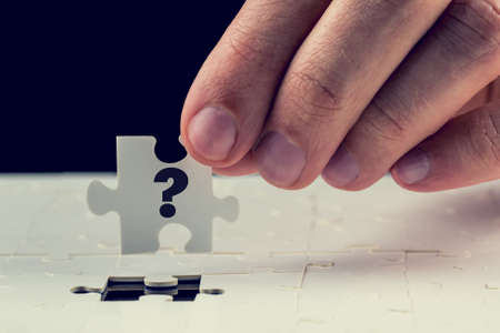 final piece of puzzle: Man holding the final puzzle piece with a question mark hand-drawn on it in his fingers above a jigsaw puzzle conceptual of a problem and the solution. Stock Photo