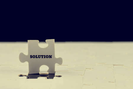 clarification: Last puzzle piece with the word - Solution - standing upright on top of a jigsaw puzzle with just the one piece missing to complete it