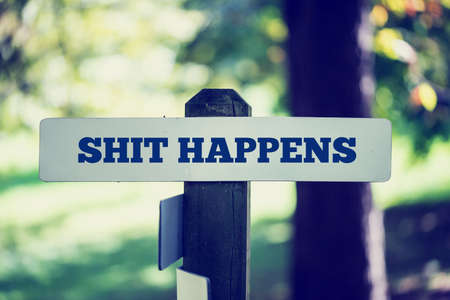 happens: Vintage faded effect image of a rustic wooden signpost in woodland with the phrase - Shit happens - in a conceptual image. Stock Photo