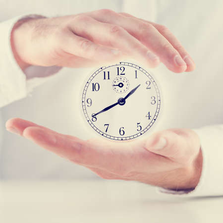 spent: Retro image of male hands making a protective gesture around clock face with white shining coming from behind it. Stock Photo
