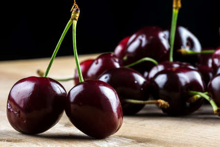 Ripe delicious red cherries on wooden board.