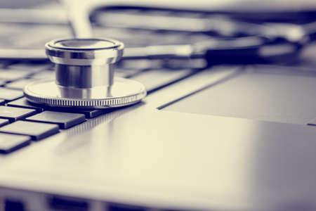 オンライン医療と医学的なアドバイス、色あせたレトロな効果の外観を描いたノート パソコンのキーボードの上に横たわる聴診器のクローズ アップ