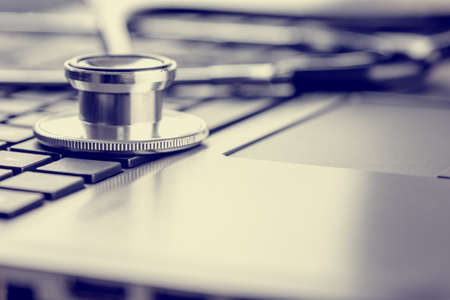 Closeup view of a stethoscope lying on a laptop keyboard depicting online healthcare and medical advice, retro effect faded look. Imagens - 28549033