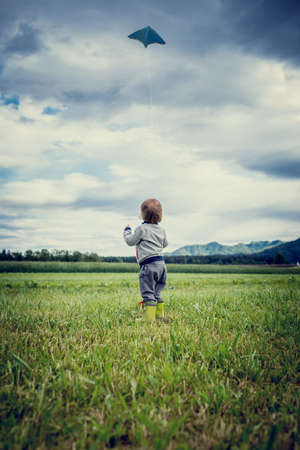 View from behind of a cute young child in gumboots standing flying a kite in a grassy green field standing holding the string watching it soar in the air above open countryside. photo