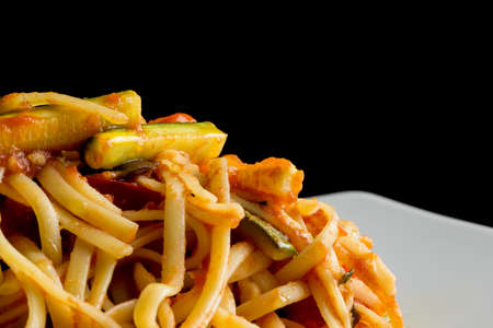 Closeup of delicious bavette pasta with vegetarian sauce over black background. photo