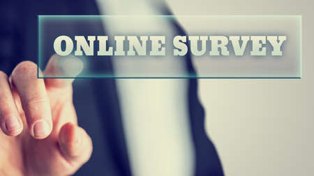 online survey: Male hand activating an Online survey button on virtual screen.