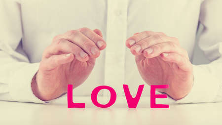 Retro image of male hands making protective or shielding gesture over word Love  Conceptual of nurturing relationship  photo