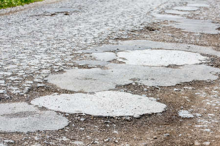 defective: Closeup of bumps and holes on a severely damaged road.