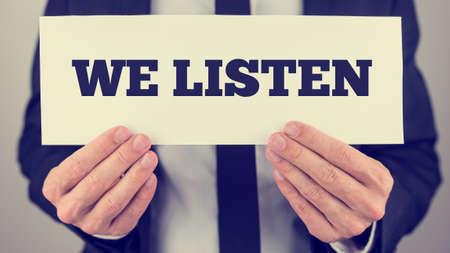 servicio al cliente: Imagen de estilo retro de las manos masculinas sosteniendo Escuchamos signo. Conceptual de la consejer�a o las buenas relaciones de servicio al cliente.