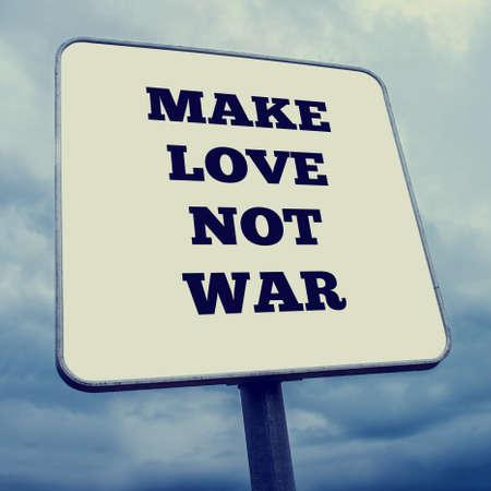 hacer el amor: Blanco se�al rectangular con las palabras - Make Love Not War - contra un cielo azul nublado ve en un �ngulo oblicuo.