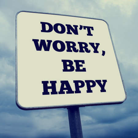 dont worry: Retro effect faded and toned image of a Dont worry, be happy billboard.