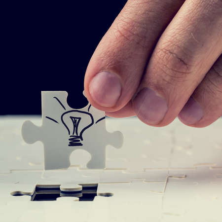 complete solution: Male hand inserting the final missing puzzle piece with light bulb drawn on it. Concept of innovation or getting a business idea.