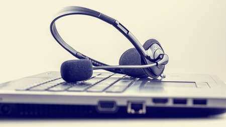 online support: Retro image of black headset on laptop keyboard. Conceptual of customer support or online chat, discussion or conference. Stock Photo