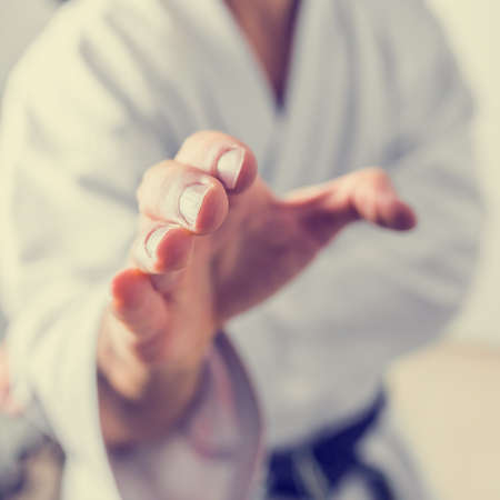 Retro effect faded and toned image of a male karate fighter making a hand gesture. photo