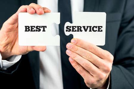 compromiso: Dos piezas de rompecabezas con la frase - El mejor servicio - repartidos en ellos y un hombre de negocios en movimiento la segunda pieza en condiciones de completar el rompecabezas.