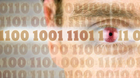 coder: Binary code with close up of human eye in the background.