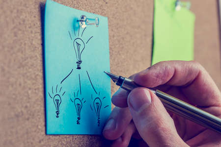 Retro image of the hand of a man working on a business plan writing on a blue sheet of paper on a notice board drawing a flow chart with light bulbs representing bright ideas. photo