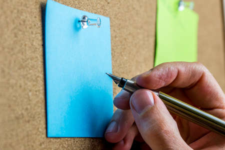 Male hand writing on blank sheet of blue paper with copyspace pinned up on a cork bulletin board. photo