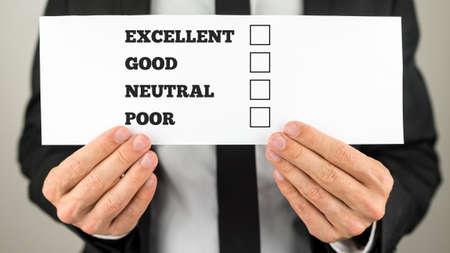 Zakenman die een enquête cheque met multiple choice selectievakjes voor uitstekend - goed - neutraal - slechte ratings.