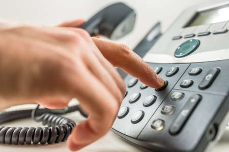Closeup of male hand dialing a phone number making a business or personal phone call. photo