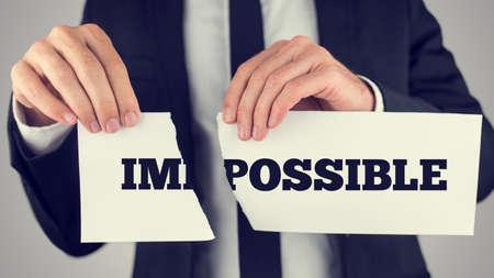 actitud positiva: Negocios que rasga un cartel que dice - Imposible - conceptual de superar con �xito los problemas y desaf�os, y actitud positiva, efecto retro descolorada.