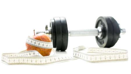 cintas metricas: Pesas, manzana y cinta de medir más de blanco Foto de archivo