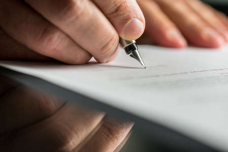 human settlement: Closeup of male hand about to sign a business contract with a fountain pen.