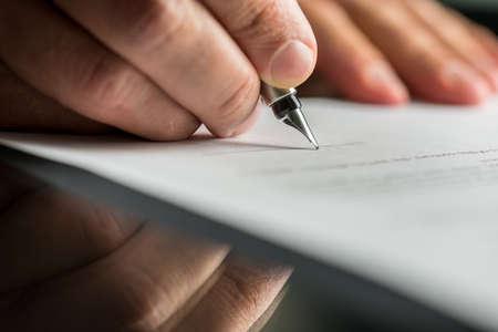 contrato de trabajo: Primer de la mano masculina a punto de firmar un contrato de negocios con una pluma estilográfica. Foto de archivo