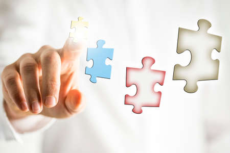 Conceptual image of business vision and plan with puzzle pieces in virtual screen with businessman arranging them with his finger.
