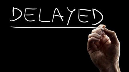 postponed: Male hand writing word Delayed on black virtual screen. Stock Photo