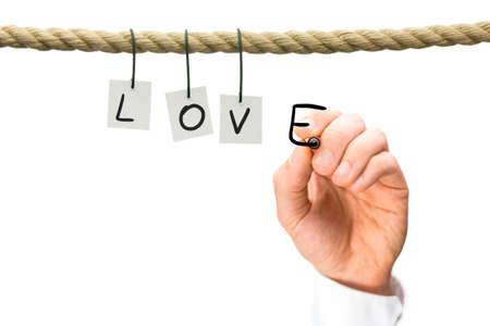 l hand: Love and romance concept with the letters L,O,V hanging from a rope across a white background and a mans hand writing the E with a black marker pen, with copyspace.