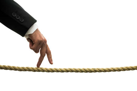 against all odds: Conceptual image of business determination with a businessman walking his fingers along a length of rope or a tightrope with perseverance and determination to succeed against all odds
