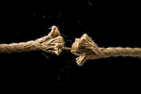 struggling: Concept of danger and risk with two ends of a frayed worn rope held together by the last strand on the point of snapping, against a dark background with copyspace.