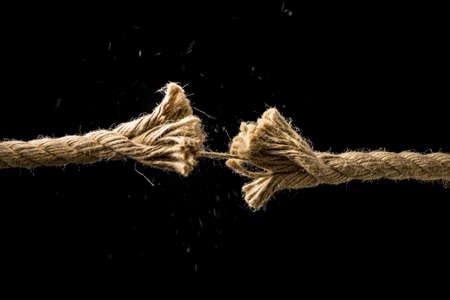 Concept van het gevaar en het risico met twee uiteinden van een gerafeld versleten touw door het laatste onderdeel bij elkaar gehouden op het punt van breken, tegen een donkere achtergrond met copyspace.